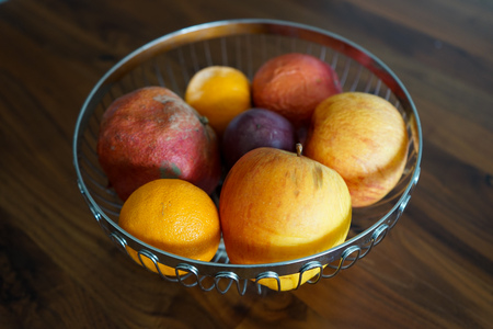 Bowl with fruits, on dark wooden table 写真素材