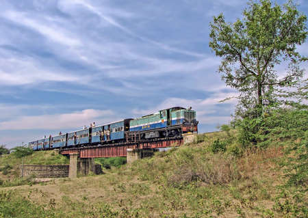 Old, 2 feet 6 inches , narrow gauge `Shakuntala` railway with few roof-top commuters crosses an old steel girder-ed bridge in Sindi, Maharashtra, India.