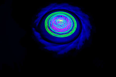 Long exposure photograph of a light spinning top with black background. Standard-Bild