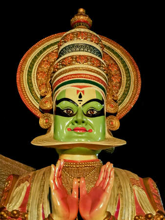 Close up image of porcelain idol face of Kerala Kathakali performer with clear black background.