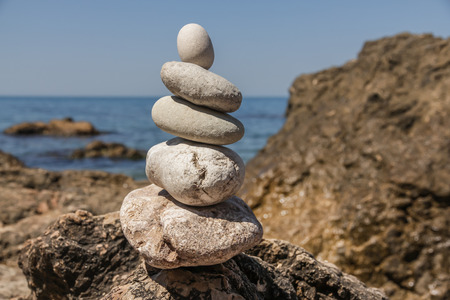 equipoise: Pebbles stacked up in a pyramid on the sea shore