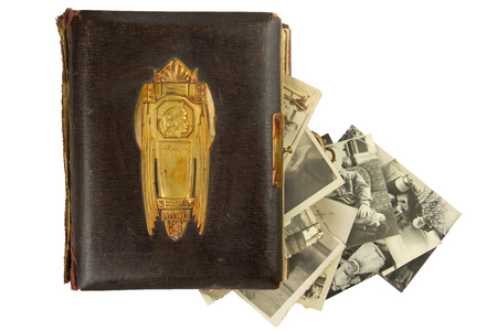 coining: Vintage photo album (circa 1900) with buckle, brass engraved decoration and falling out retro photos (circa 50s) isolated on white Stock Photo