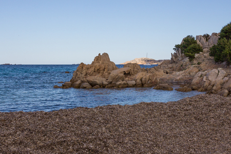 Costa Smeralda seascape with rocks and a sailing boat. Beach in Sardinia island, Italy Banco de Imagens