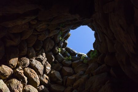 View to the sky from the dome of ancient megalithic Nuraghe tower, the symbol of Sardinia, Italy