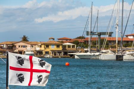 PORTO ROTONDO, SARDINIA, ITALY - MAY 2019: The flag of Sadinia on the sardinian coast Costa Smeralda 版權商用圖片 - 124156145