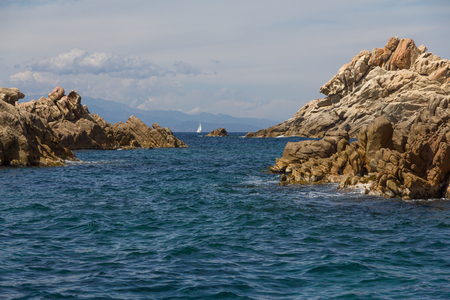 Costa Smeralda seascape with rocks and a sailing boat. Sardinia island, Italy