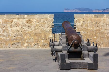 Historical cannon in old town of Alghero pointing to the sea, with a view on cape Capo Caccia. 版權商用圖片 - 130745475