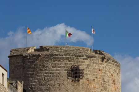 ALGHERO, SARDINIA, ITALY - JULY 2019: Torre di Porta Terra with three flags - catalan, italian and sardinian