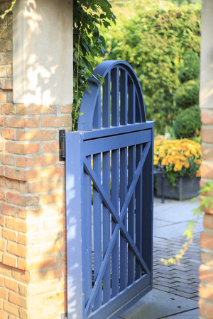 ivy hanging: Open Blue Gate Leading into Garden with Brick Wall and Hanging Ivy