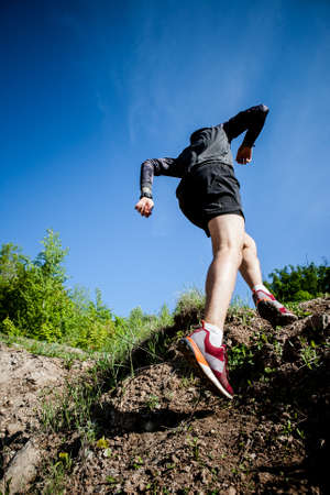 young adult sports guy trail runner practicing sunny day in the mountains