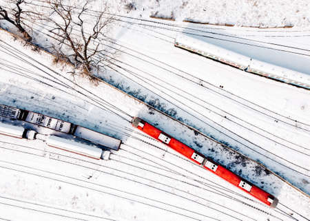 Top view of cargo trains and passanger diesel multiple unit - DMU. Aerial top view from flying drone of snow covered freight trains on the railway tracks.