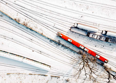 Top view of cargo trains and passanger diesel multiple unit - DMU. Aerial top view from flying drone of snow covered freight trains on the railway tracks and trees without leaves.