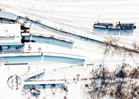 Top view of cargo trains and locomotive depot. Aerial view from flying drone of snow covered freight trains on the railway station.