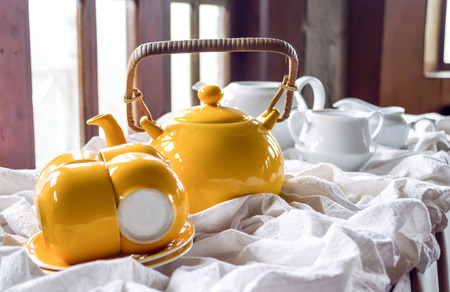 yellow teapot with a cup and saucer and white teapot