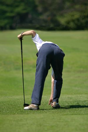 A golfer setting up a ball on a golf course   photo