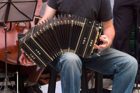 Musician plays tango with bandoneon in the street.