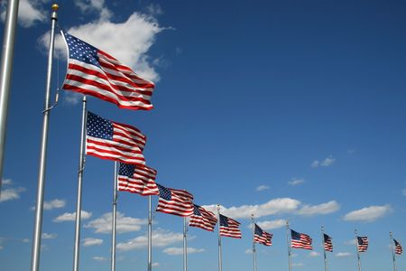 American flags flying with blue sky background.
