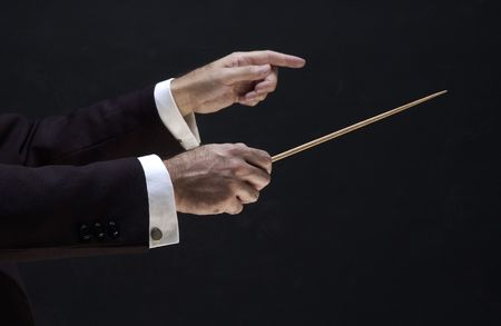 symphony: hands of the conductor, on black background