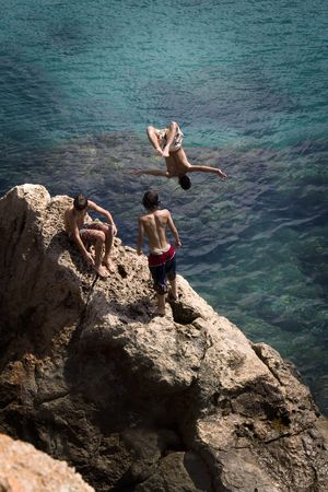 Children jumping into the sea from a rock in Ibiza Stock Photo