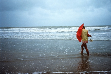 Young woman walking on the beach in the rain photo