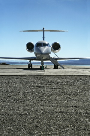 Front View of a Lear jet on a tarmac ready to fly with passengers. photo