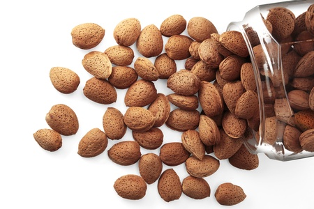 Almonds in a glass jar on white background