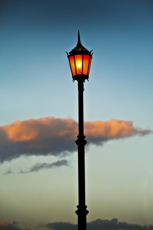 Lit old streetlamp at sunset in Argentine  photo