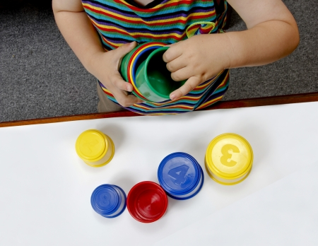 Baby playing with plastic cups educational Stock Photo