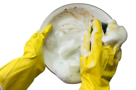 A pair of hands with yellow gloves washing a dirty dish