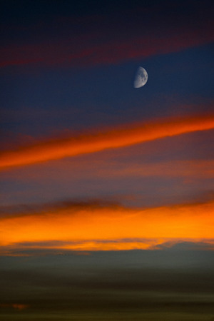 Moon in a waning quarter stands out against the sunset sky.