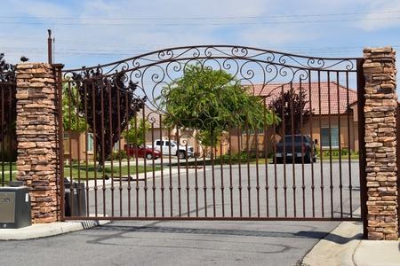 wrought iron ornate metal gate with slate stone pillars Banco de Imagens