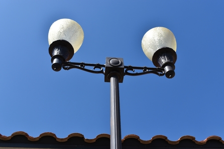 tall erect street lamps with frosted white glass globes Imagens