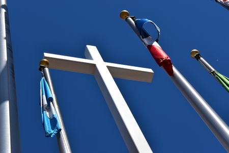 Tall white cross reaching the sky with surrounded flags Imagens