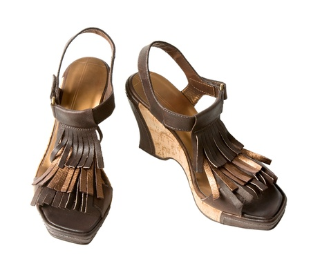 ankle strap: Wedge fringed leather sandals, isolated on white. Clipping path included. Stock Photo
