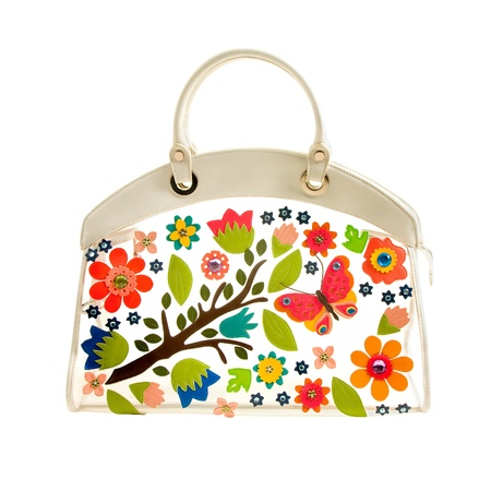 naif: Transparent white leather handbag with colorful leather flowers and crystals isolated on white background. Clipping path included Stock Photo