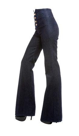 cintura: Las piernas de la mujer joven con cuatro botones de los pantalones vaqueros de campana de oro de la plataforma y tacones de aguja aisladas en el sendero blanco de recorte fondo incluido