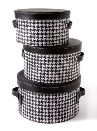 Set of houndstooth check and black leather bandboxes isolated on white background Stock Photo
