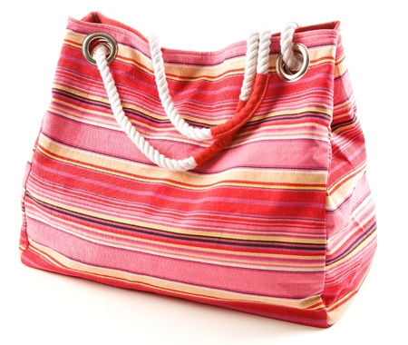 Pinkish canvas striped beach bag with rope shoulder strap isolated on white background  photo