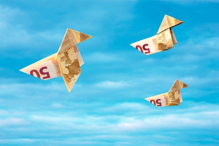 imposition: Bank note origami paper birds flying away on blue sky  Abstract concept of money flying away during crisis