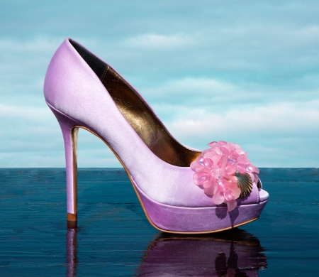 Lilac fashionable stiletto peep toe with marine golden details on reflective wet surface  photo