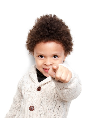 incriminate: Cute child smiling and pointing at you isolated on white background