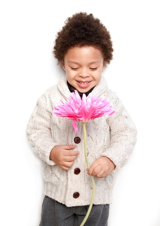 Cute child holding a big pink flower and looking at it isolated on white background  photo