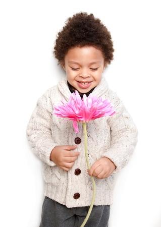 ni�os negros: Ni�o lindo celebraci�n de una gran flor rosa y mirando a ella aislados en fondo blanco