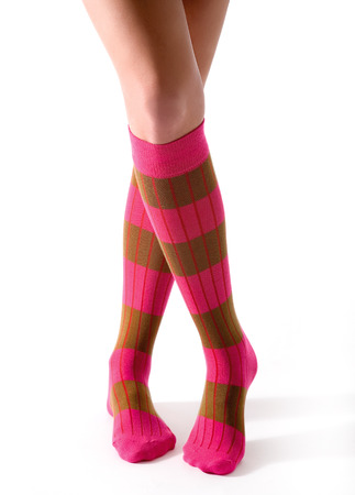 Young woman crossed legs posing with pink striped socks isolated on white background