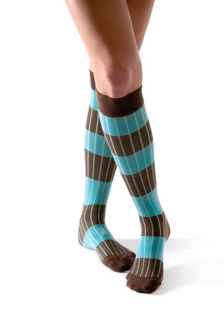 Young woman crossed legs posing with turquoise striped socks isolated on white background  Stock Photo