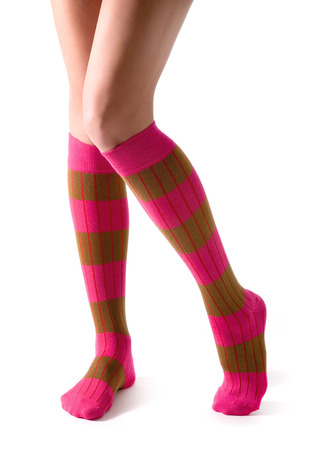 Young woman legs posing with pink striped socks isolated on white background