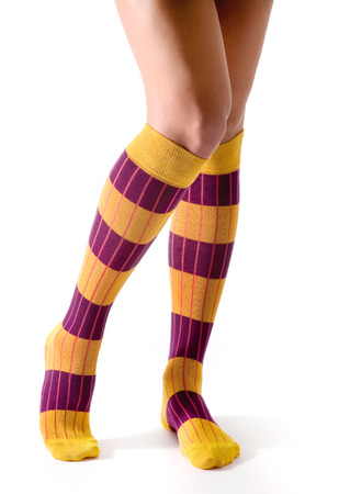 Young woman legs posing with purple and yellow striped socks isolated on white background