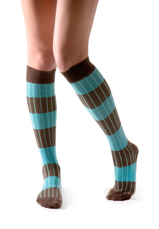 Young woman legs posing with turquoise striped socks isolated on white background