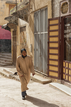 MEKNES, MOROCCO - FEBRUARY 18, 2017: Unidentified woman walking in the street of Meknes, Morocco. Meknes is one of the four Imperial cities of Morocco.