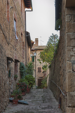 Montichiello - Italy, October 29, 2016: Quiet street in Montichiello, Tuscany with typical shuttered windows and paved streets. Monticchiello is the only fraction of the municipality of Pienza, in the province of Siena. It is a typical medieval village im